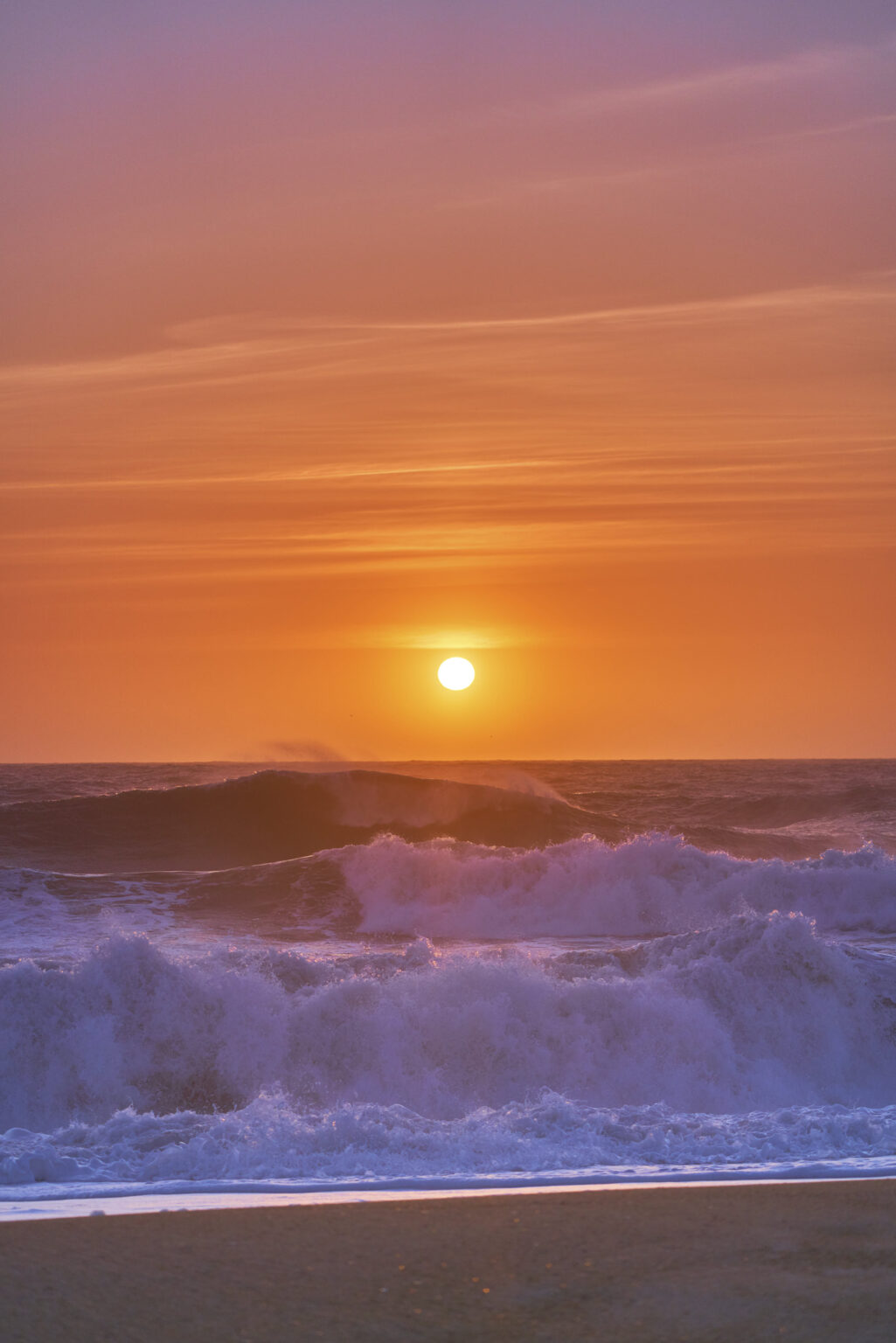 Sun setting on Nazare Beach as the surf crashes in